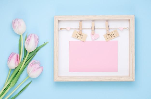 Amor y besos inscripción en marco con flores de tulipán.