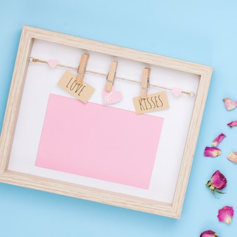 Amor y besos inscripción en marco con pétalos de flores.