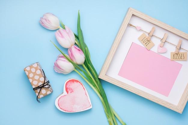 Amor y besos inscripción en marco con tulipanes y regalo.