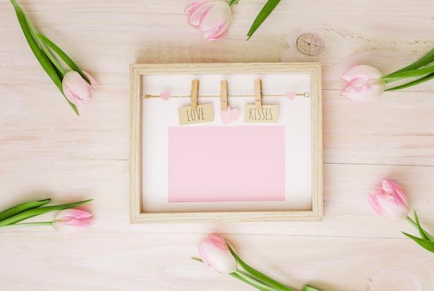 Amor y besos inscripción en marco con tulipanes.