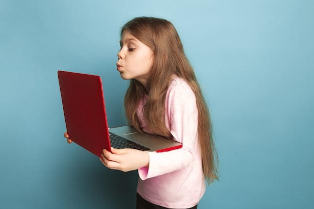 El amor por la computadora. muchacha adolescente con el cuaderno en un azul.