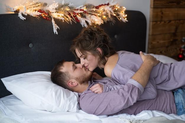 Amor día de san valentín pareja acostada en la cama, sonrisa feliz mirando el uno al otro