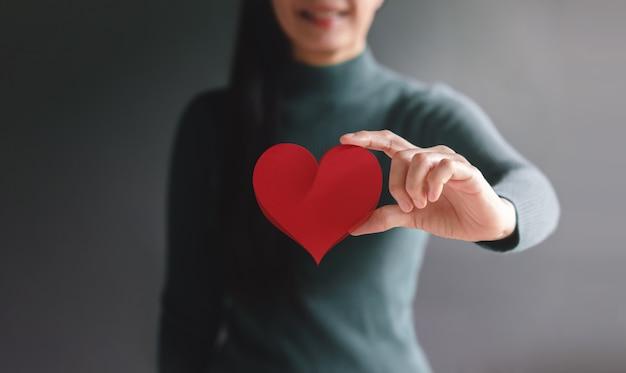 Amor donación de atención médica y concepto de caridad sonriente mujer voluntaria sosteniendo un corazón