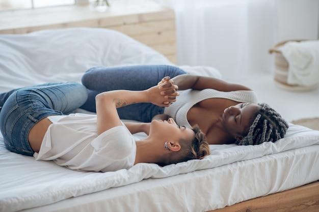 Amor. dos niñas, acostado, en la cama, y, tomados de la mano