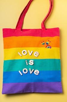 El amor es la bolsa reutilizable del arco iris del texto del amor contra el fondo amarillo