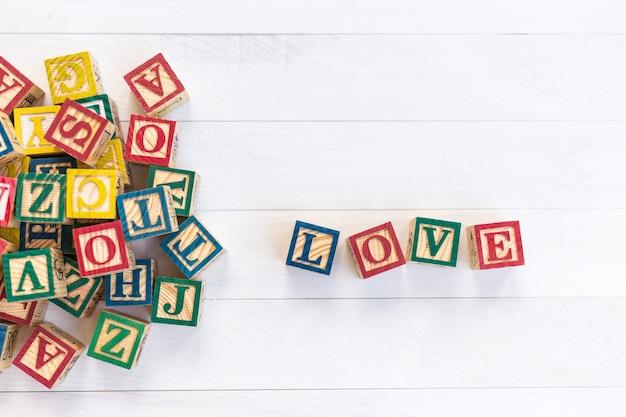 Amor escribir en bloque de madera del alfabeto sobre fondo blanco de tablero de madera