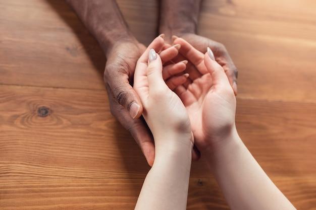 Amor, familia, apoyo, amistad. cerca de las manos femeninas caucásicas y masculinas afroamericanas sosteniendo. concepto de relación, confianza y seguridad, mano amiga, ternura y calidez.