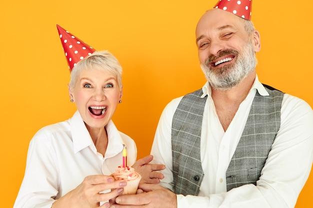 Amor, familia, celebración, alegría y felicidad. hermosa mujer madura de pelo corto lleno de alegría celebrando el aniversario de boda con su marido barbudo, vistiendo sombreros de cono y soplando velas en la torta de la taza