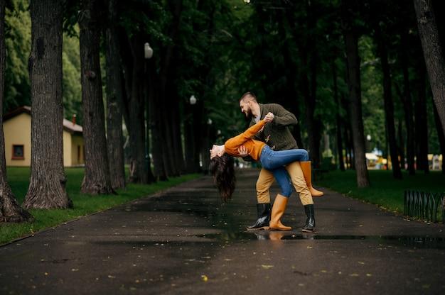 Amor feliz pareja bailando en el parque en verano día lluvioso. hombre y mujer abrazos bajo el paraguas bajo la lluvia, cita romántica en el sendero, clima húmedo en el callejón