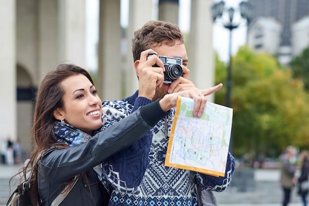 Amor feliz pareja de turistas tomando fotos en excursión o recorrido por la ciudad. viaja junto con un mapa y una cámara retro.