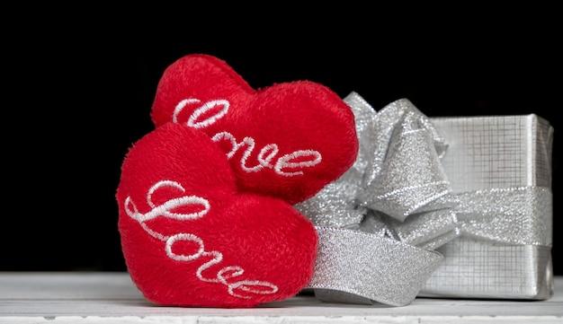 Amor en forma de corazón rojo y caja de regalo plateada en tabel de madera blanca sobre oscuro