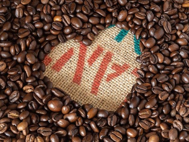 Amor forma granos de café sobre fondo de textura de lino