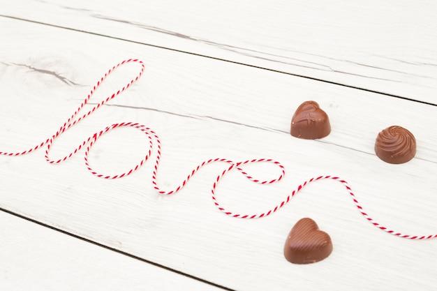 Amor inscripción de hilo cerca de corazones de chocolate.