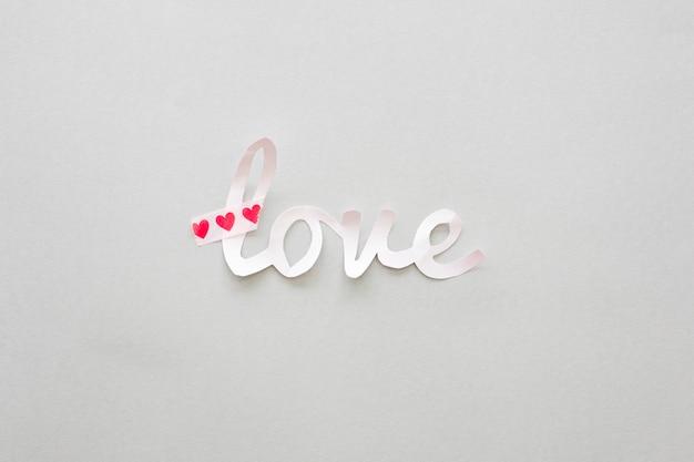 Amor inscripción de papel con corazones en mesa