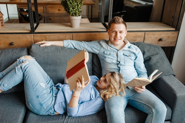 Amor joven pareja descansando en un cómodo sofá en casa.