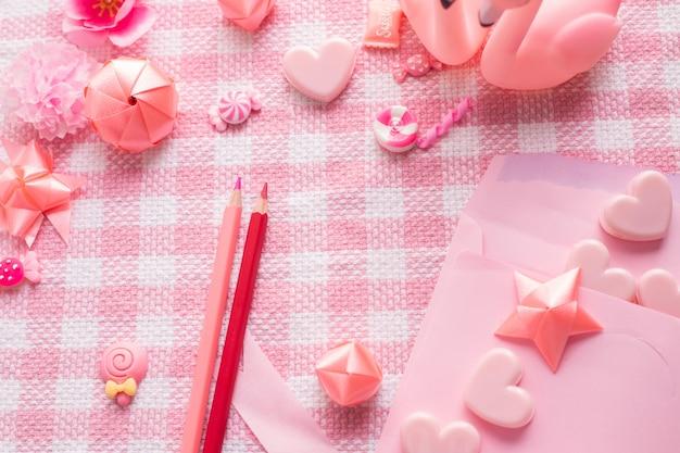 Amor de la letra y decoración del día de tarjeta del día de san valentín en fondo rosado de la textura del mantel.