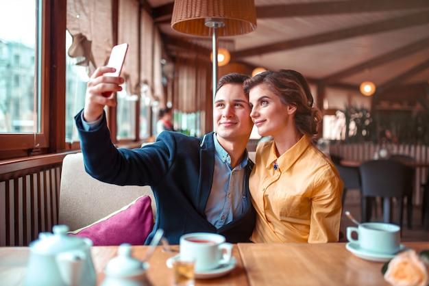 Amor pareja abrazos y hace selfie en la cámara del teléfono