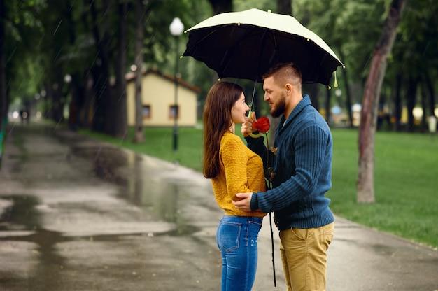 Amor pareja con abrazos de paraguas en el parque de verano en día lluvioso. hombre y mujer con rosa en sendero bajo la lluvia, clima húmedo en el callejón