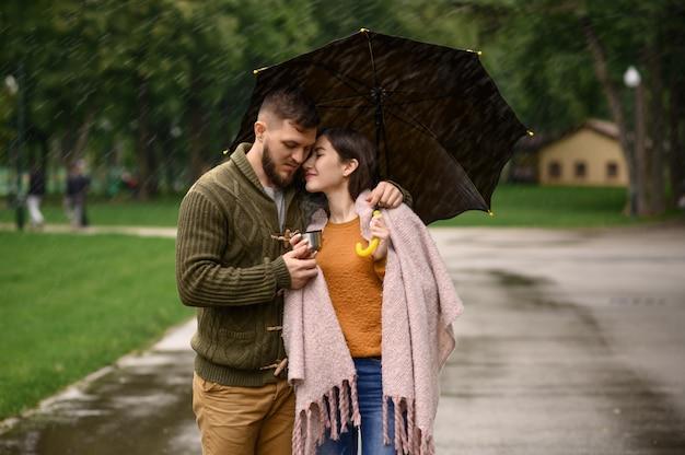 Amor pareja bebe café caliente en el parque, día lluvioso de verano. el hombre y la mujer están parados bajo el paraguas bajo la lluvia, cita romántica en el sendero, clima húmedo en el callejón