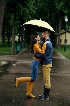 Amor pareja besándose en el parque, día lluvioso de verano. el hombre y la mujer están parados bajo el paraguas bajo la lluvia, cita romántica en el sendero, clima húmedo en el callejón