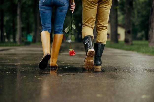 Amor pareja camina en el parque, día lluvioso de verano. hombre y mujer ocios juntos, cita romántica en sendero, clima húmedo en el callejón