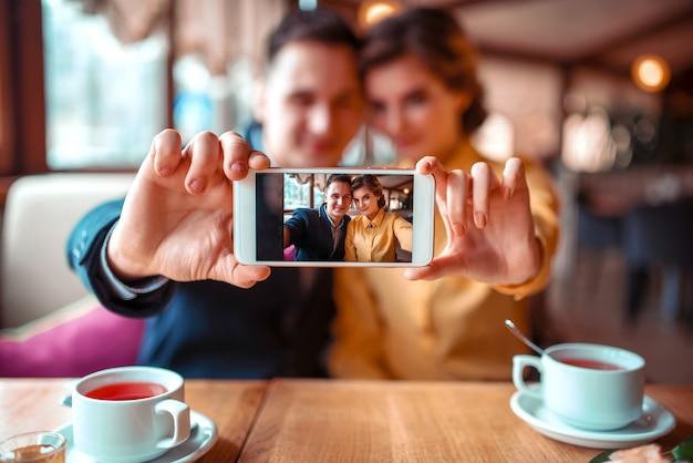 Amor pareja hace selfie en cámara en restaurante