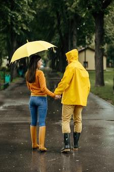 Amor pareja con paraguas caminando en el parque de verano en día lluvioso. el hombre y la mujer con botas de goma en el sendero, clima húmedo en el callejón