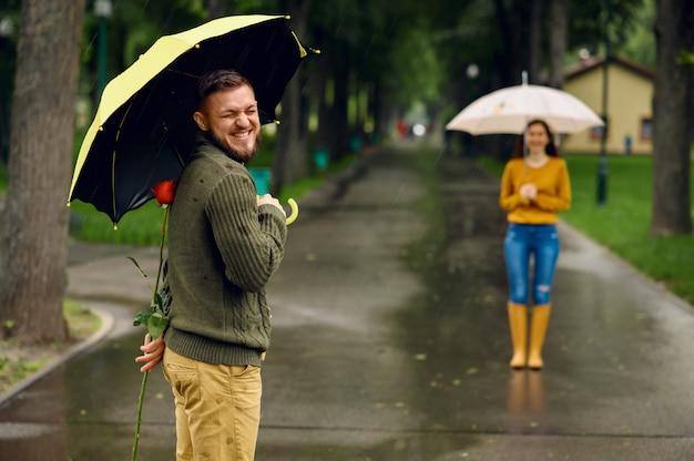 Amor pareja con paraguas se encuentra en el parque, día lluvioso. hombre con rosa roja esperando a su mujer en el sendero, clima húmedo en el callejón