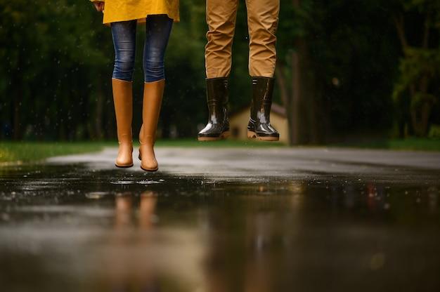 Amor pareja salta en un charco en el parque, día lluvioso de verano. hombre y mujer bajo el paraguas bajo la lluvia, cita romántica en el sendero, clima húmedo en el callejón