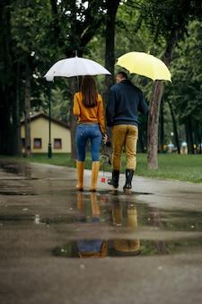 Amor pareja con sombrillas camina en el parque de verano, vista posterior, día lluvioso. hombre y mujer ocios en sendero bajo la lluvia, clima húmedo en el callejón