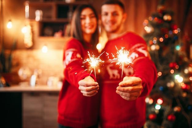 Amor pareja tiene luces de bengala en las manos, navidad
