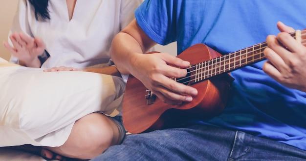 Amor pareja tocando el ukelele y la guitarra en la cama
