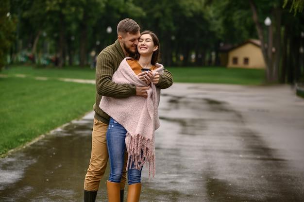 Amor pareja tomar el sol uno contra el otro en el parque, día lluvioso de verano. el hombre y la mujer están parados bajo el paraguas bajo la lluvia, cita romántica en el sendero, clima húmedo en el callejón