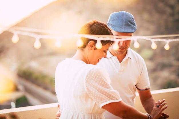 Amor y romántica pareja caucásica de mediana edad bailando y permanecer juntos con amor y romance en la terraza de casa con vista