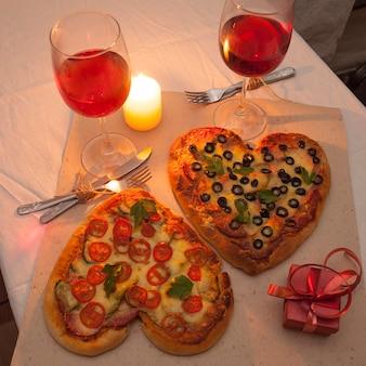 Amor romántico cena de pizza en forma de corazón y regalos.