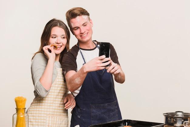 Amores haciendo fotos en la cocina