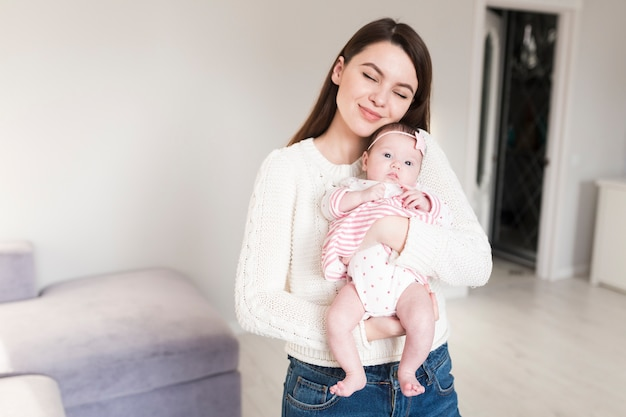 Amorosa madre con bebé en las manos