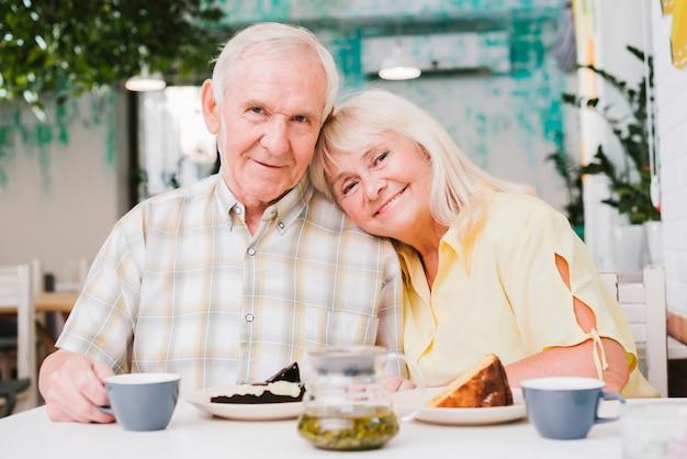 Amorosa pareja de ancianos bebiendo té y comiendo pastel