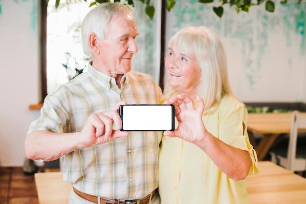 Amorosa pareja de ancianos mostrando teléfono inteligente a la cámara