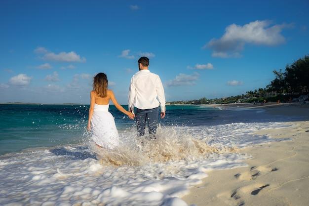 Amorosa pareja bailando en la arena de la playa del mar en verano contra el agua azul cristalina