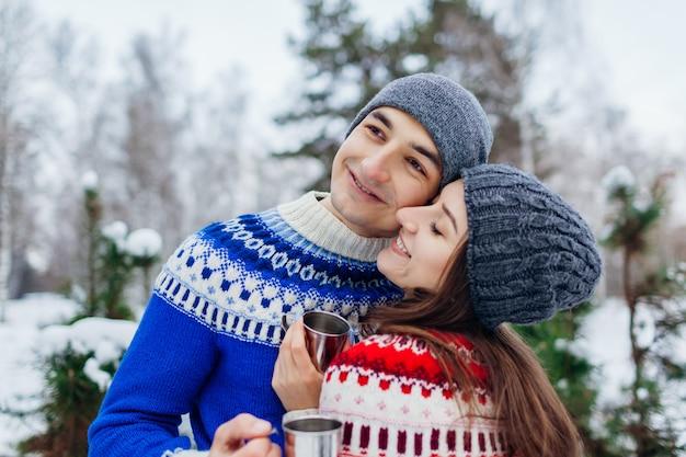 Amorosa pareja bebiendo té en bosque de invierno