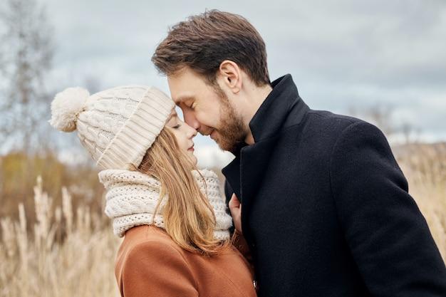 Amorosa pareja caminando en el parque en otoño abrazos y besos.
