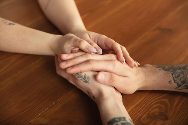 Amorosa pareja cogidos de la mano de cerca en la mesa de madera