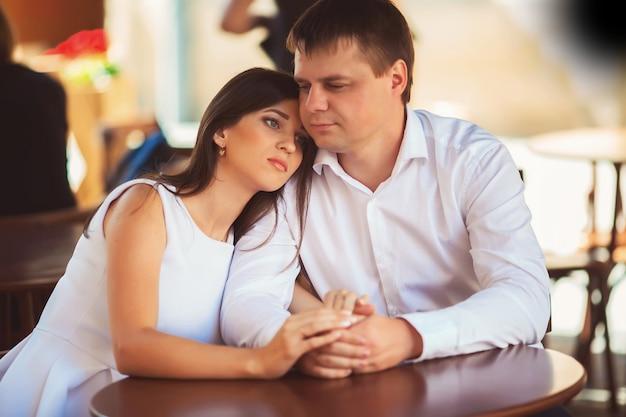 Amorosa pareja cogidos de la mano, sentado en la cafetería