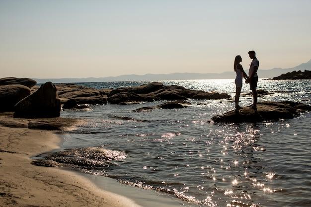 Amorosa pareja de pie en el mar al atardecer