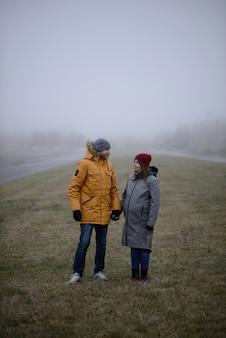 Amorosa pareja embarazada está caminando fuera de la ciudad a finales de otoño.