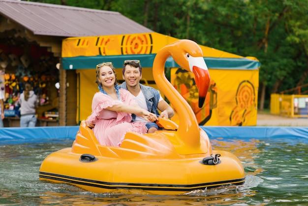 Amorosa pareja feliz montando una moto de agua en forma de flamencos en el parque de diversiones, sonríen