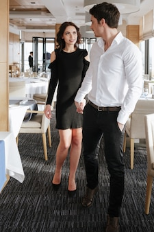 Amorosa pareja feliz de pie y tomados de la mano el uno del otro