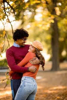 Amorosa pareja hermosa hombre afroamericano y mujer caucásica caminando en el parque de otoño