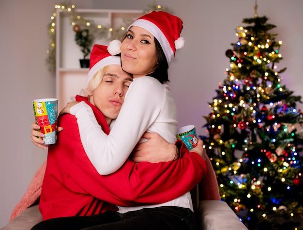 Amorosa pareja joven en casa en la época de navidad con gorro de papá noel sentado en un sillón sosteniendo vasos de plástico de navidad abrazándose chica mirando a la cámara chico con los ojos cerrados en la sala de estar